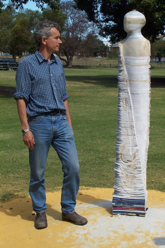 Photo of Artist Graham Hay with sculpture called Bureaucrat I, which was made in 2002.  This is an outside sculpture made from Government documents.  It measures 200 x 40 x 20 cm.  Photo by Frances Dennis.