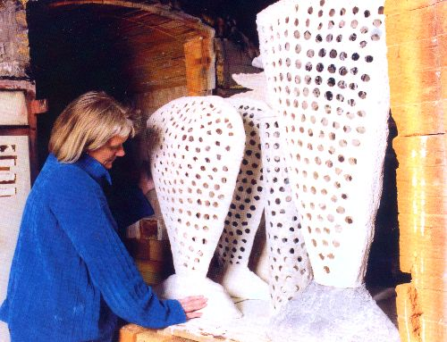 Picture of Rosette Cault places paperclay forms in the kiln.